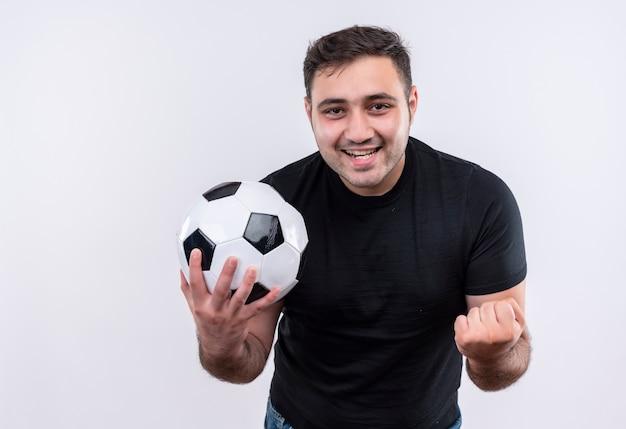 Jonge man in zwart t-shirt met voetbal bal l gebalde vuist blij en opgewonden staande over witte muur Gratis Foto