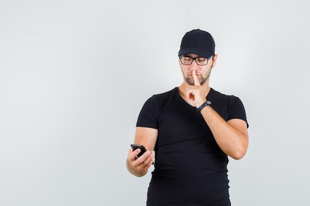 Jonge man in zwart t-shirt, pet, bril smartphone met stilte gebaar kijken Gratis Foto