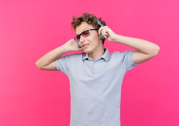 Jonge man in zwarte bril met grijs poloshirt met koptelefoon glimlachend vrolijk genietend van favoriete muziek staande over roze muur Gratis Foto