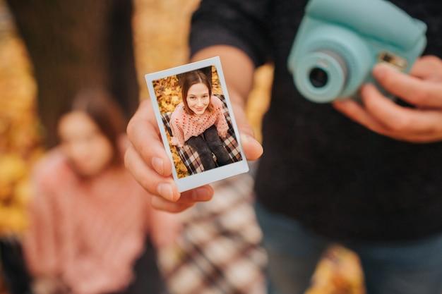 Jonge man in zwarte kleding toont foto in één hand en camera in een andere. er zijn jonge vrouw op foto. ze zit naast hem op een deken. Premium Foto