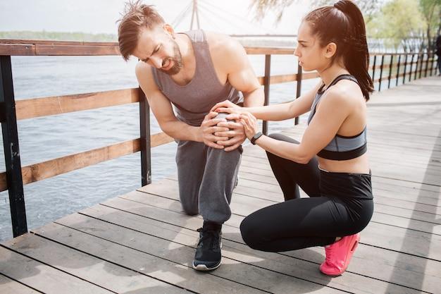 Jonge man is op de brug met zijn vriendin. hij heeft pijn in zijn knie. Premium Foto