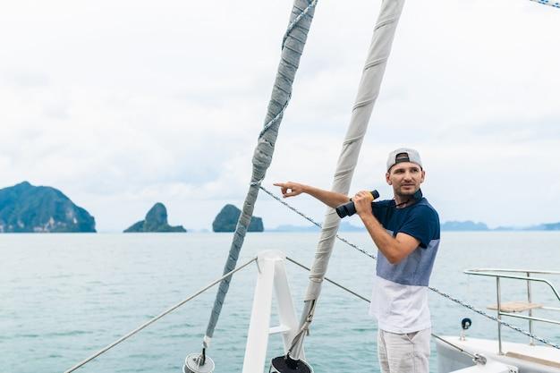 Jonge man jacht kijkt door een verrekijker. reizen en actief leven. Premium Foto