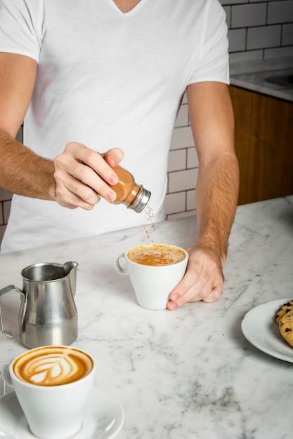 Jonge man kaneel toe te voegen in een kopje cappuccino Gratis Foto