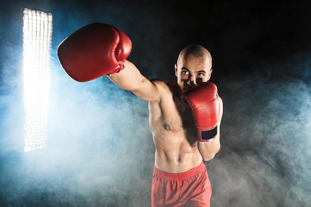 Jonge man kickboksen in blauwe rook Gratis Foto