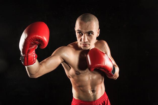 Jonge man kickboksen op zwart Gratis Foto