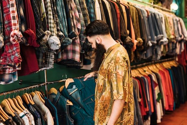 Jonge man kleding op een rek in een showroom te kiezen Gratis Foto