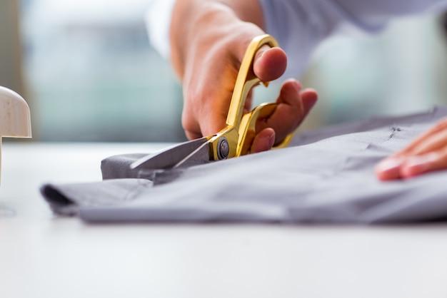 Jonge man kleermaker bezig met nieuwe kleding Premium Foto