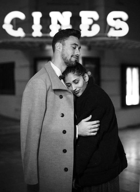 Jonge man knuffelen charmante aantrekkelijke vrouw op straat Gratis Foto