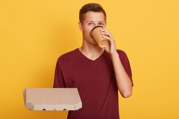 Jonge man koffie drinken en grote pizza in handen houden Premium Foto