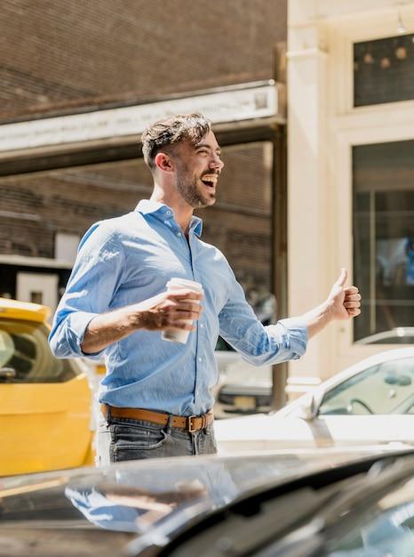 Jonge man koffie drinken en taxi plukken Gratis Foto