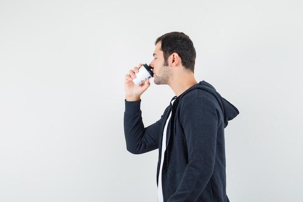 Jonge man koffie drinken in wit t-shirt en zwarte hoodie met ritssluiting en op zoek kalm, vooraanzicht. Gratis Foto