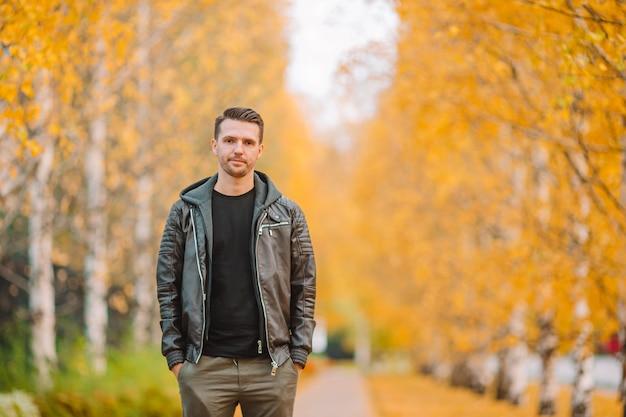 Jonge man koffie drinken met telefoon in herfst park buitenshuis Premium Foto