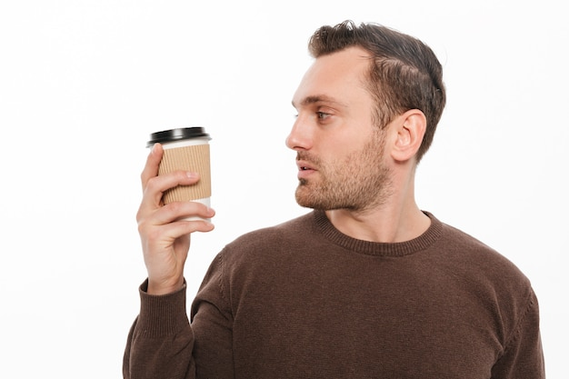 Jonge man koffie drinken. opzij kijken. Gratis Foto