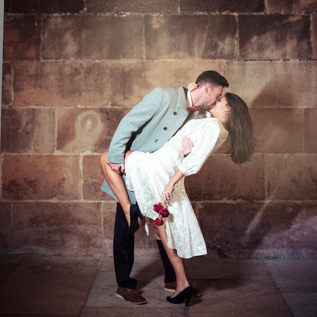 Jonge man kussende vrouw in straat Gratis Foto