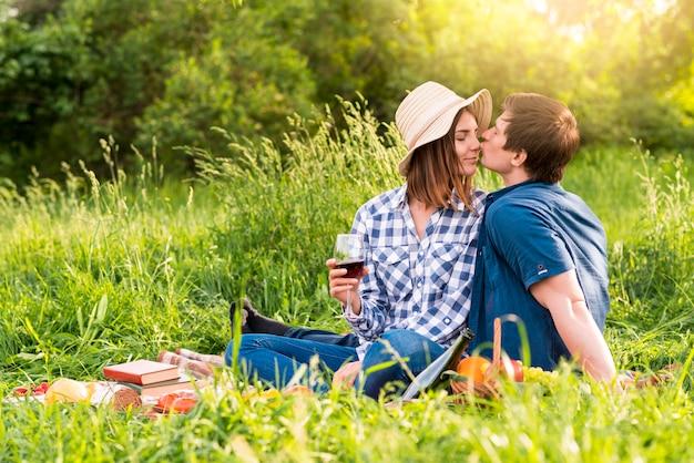 Jonge man kussende vrouw op picknick Gratis Foto