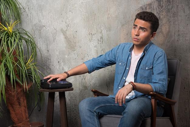 Jonge man legde de telefoon neer en zat op een stoel. hoge kwaliteit foto Gratis Foto