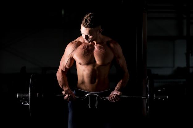 Jonge man lift een barbell in de sportschool Gratis Foto