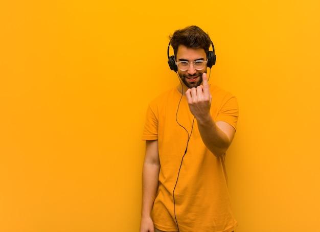Jonge man luisteren naar muziek die uitnodigt om te komen Premium Foto
