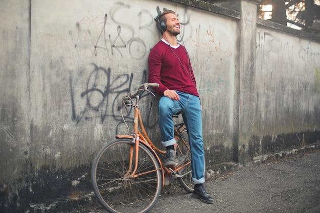 Jonge man luisteren naar muziek en glimlachend staande tegen een muur op straat Gratis Foto