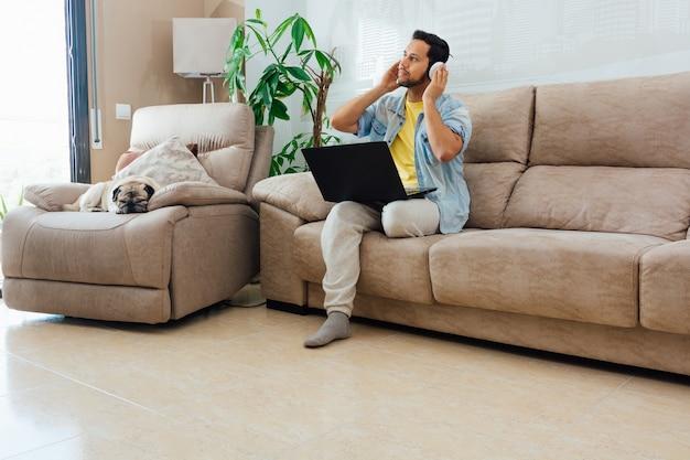 Jonge man, luisteren naar muziek met een koptelefoon en met behulp van een laptop om vanuit huis te werken Gratis Foto