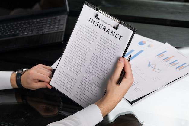 Jonge man maakt kennis met verzekeringsvoorwaarden in heldere kantoor Premium Foto