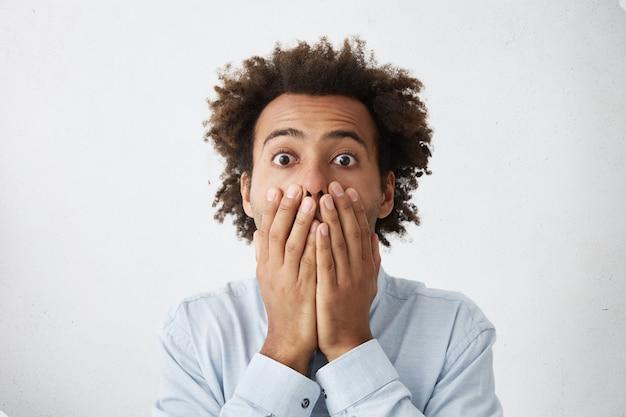 Jonge man met afro kapsel voor mond en camera kijken met bang uitdrukking op zijn gezicht Gratis Foto