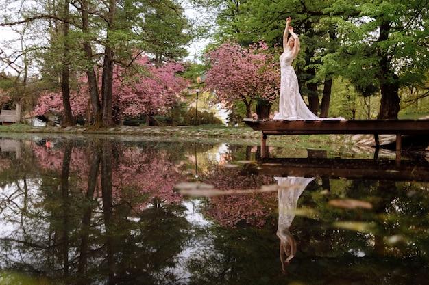 Jonge man met baard en bruid in luxe lange jurk knuffelen in de buurt van meer in park met bloeiende kersen of sakura bloesems. bruiloft lente Premium Foto