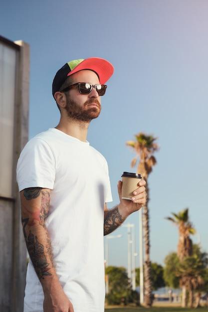 Jonge man met baard en tatoeages in wit t-shirt zonder label met een koffiekopje tegen blauwe lucht en palmbomen Gratis Foto