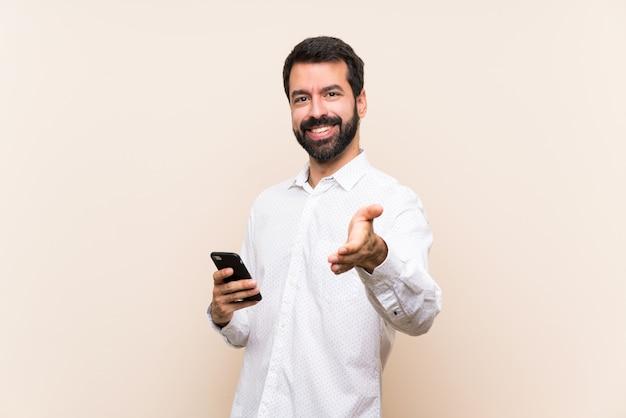 Jonge man met baard met een mobiele handen schudden voor het sluiten van een goede deal Premium Foto