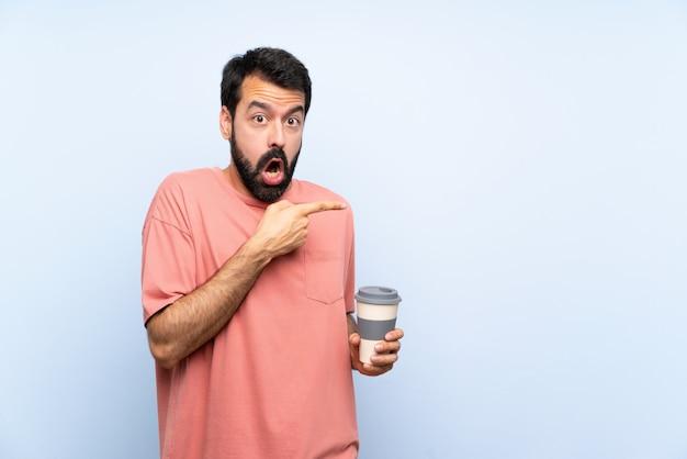 Jonge man met baard met een take-away koffie over geïsoleerde blauwe verrast en wijzende kant Premium Foto