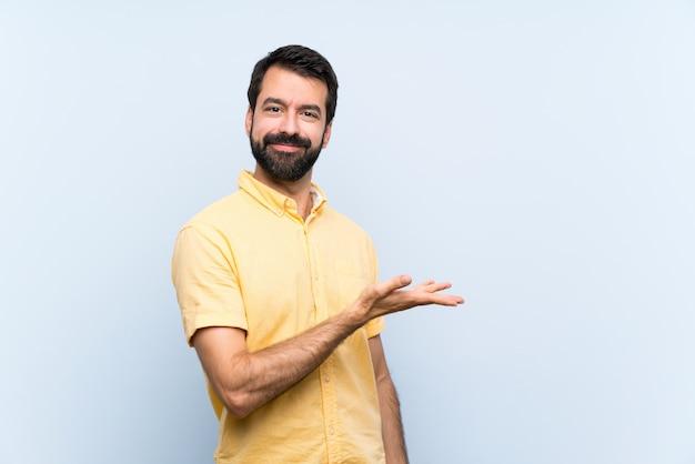 Jonge man met baard op blauw presenteren van een idee terwijl op zoek glimlachen naar Premium Foto
