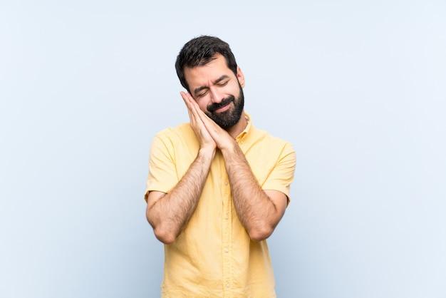 Jonge man met baard op blauw slaapgebaar in schattige uitdrukking Premium Foto
