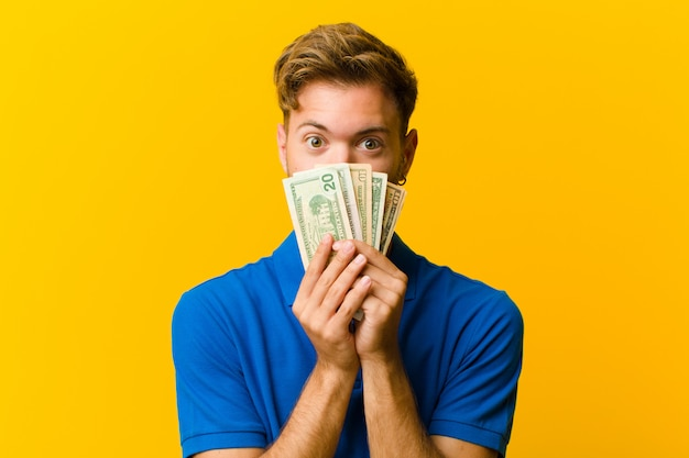 Jonge man met bankbiljetten tegen sinaasappel Premium Foto