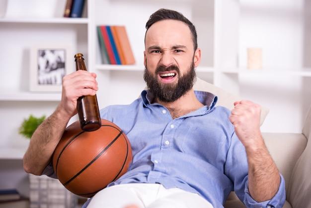 Jonge man met basketbal en bier kijkt naar het spel. Premium Foto