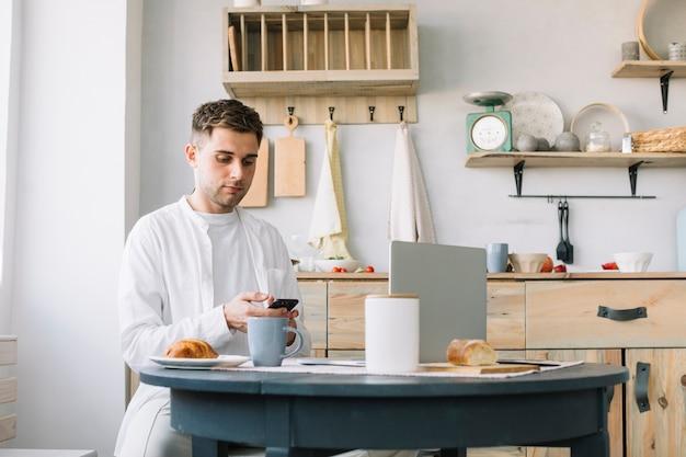 Jonge man met behulp van de smartphone zitten in de buurt van de tafel met ontbijt en laptop in de keuken Gratis Foto