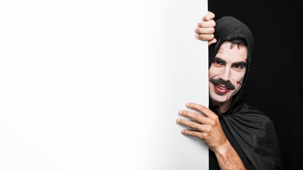 Jonge man met bleke gezicht in zwarte mantel poseren in studio Gratis Foto