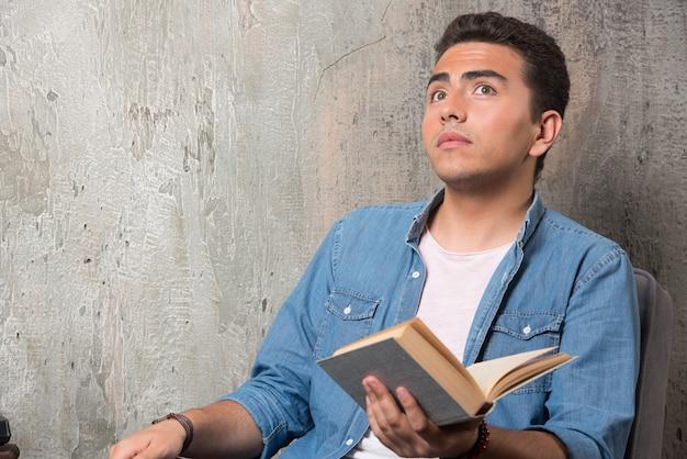 Jonge man met boek opzoeken en zittend op een stoel. hoge kwaliteit foto Gratis Foto