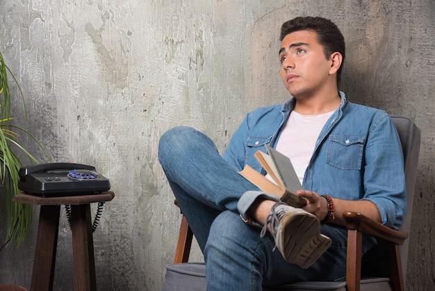 Jonge man met boek opzoeken en zittend op een stoel op marmeren achtergrond. hoge kwaliteit foto Gratis Foto