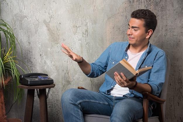 Jonge man met boek zittend op een stoel op marmeren achtergrond. hoge kwaliteit foto Gratis Foto