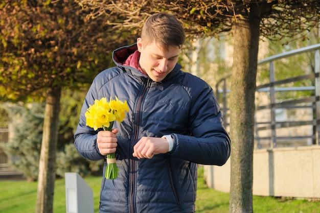 Jonge man met boeket van lentebloemen kijkt naar polshorloge Premium Foto