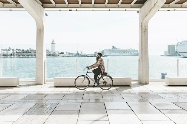 Jonge man met de fiets in de buurt van de haven Gratis Foto