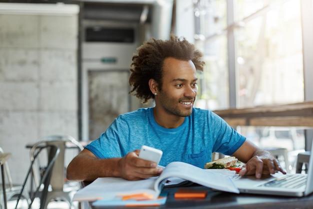 Jonge man met donkere huid en krullend haar omringd door boeken met telefoon in zijn hand kijken in laptop met glimlach blij te vinden wat hij nodig heeft voor project. mensen, jongeren, onderwijs Gratis Foto