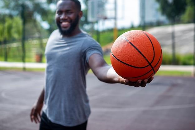 Jonge man met een bal medium schot Gratis Foto