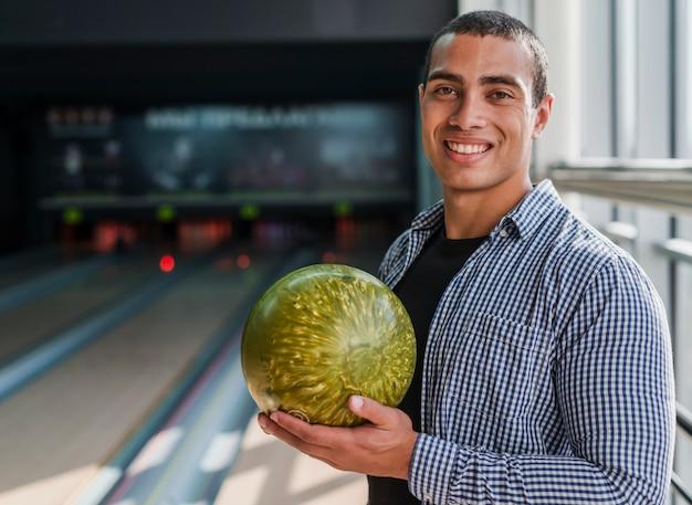 Jonge man met een gouden bowlingbal Gratis Foto