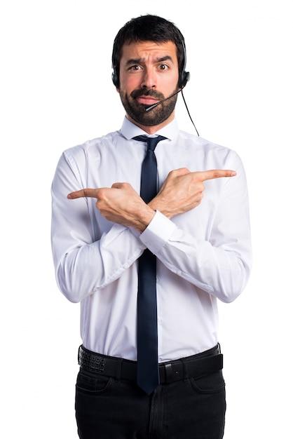 Jonge man met een hoofdtelefoon die naar de laterals wijst en twijfels heeft Gratis Foto