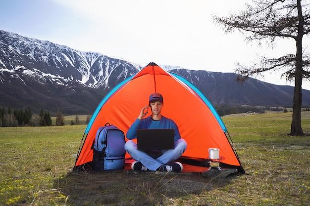 Jonge man met een laptop in een tent tegen de bergen en heuvels van altai zitten en praten op een mobiele telefoon. het concept van werken op afstand of freelancer levensstijl Premium Foto