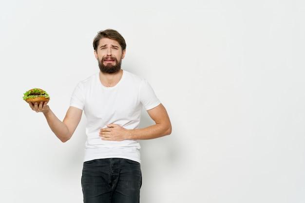 Jonge man met een sappige hamburger in zijn handen, een man die een hamburger eet Premium Foto