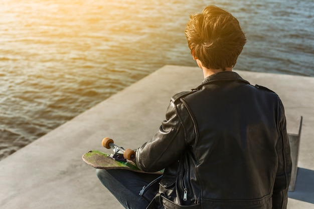 Jonge man met een skateboard in de buurt van de zee Gratis Foto