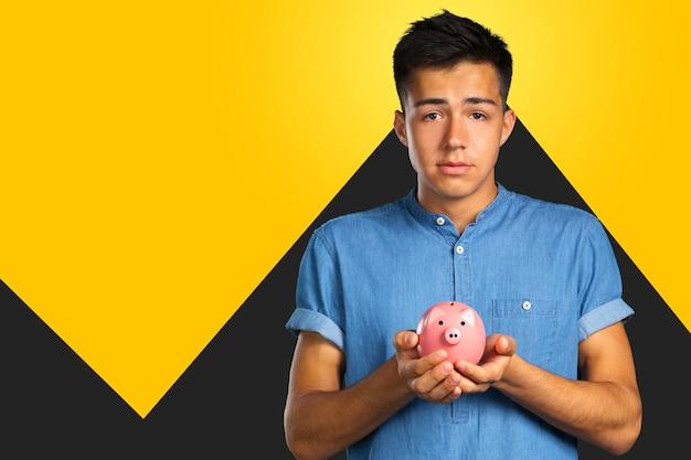 Jonge man met een spaarvarken Premium Foto