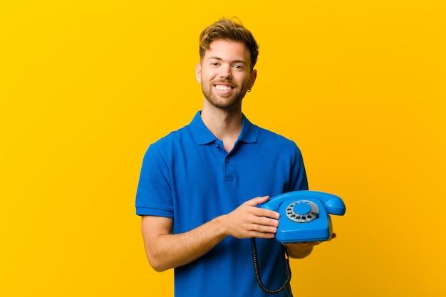 Jonge man met een telefoon tegen oranje achtergrond Premium Foto